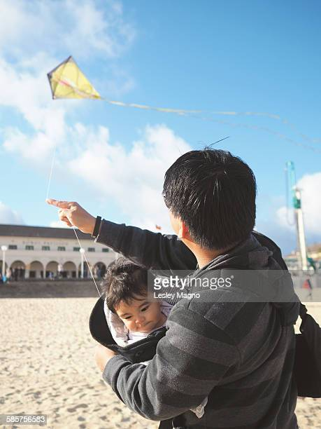 Dad is flying a kite while carrying baby son