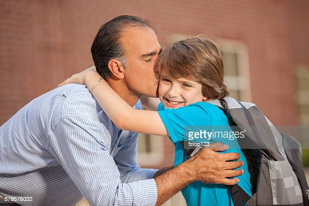 Dad kisses boy goodbye on first day of school.