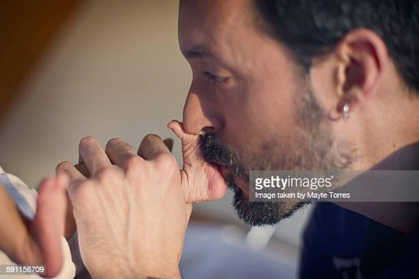 Dad kissing newborn feet at hospital