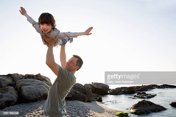 dad lifts young son above his head on beach - vertrauen stock-fotos und bilder