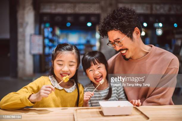 dad & little daughters having local snacks joyfully in a snack shop - hong kong stock pictures, royalty-free photos & images