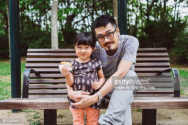 dad & little girl smiling at the camera in park - leanintogether stock pictures, royalty-free photos & images