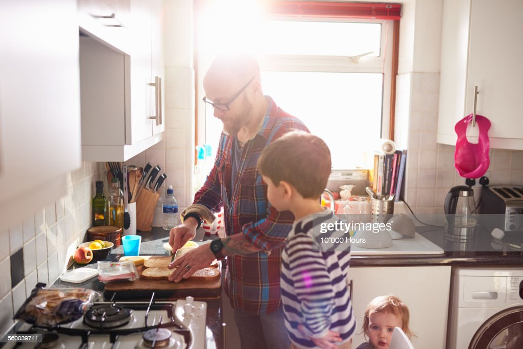 Dad making lunch for his children : Stock Photo