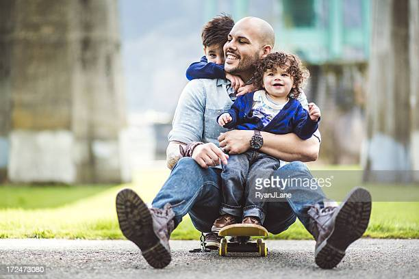 Vater auf einem skateboard in einem park mit seinen zwei Söhnen
