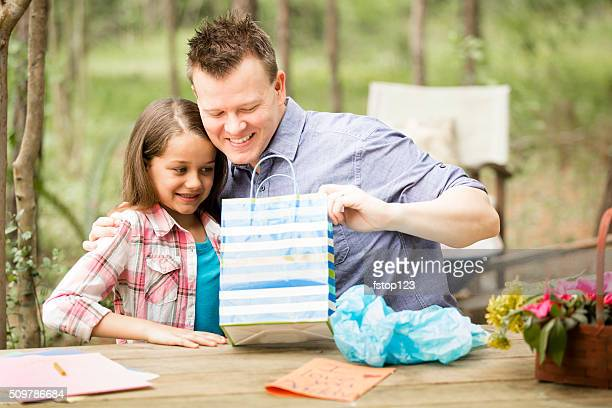 Dad opens Father's Day gift from daughter outdoors. Child, parent.