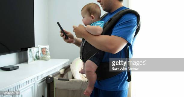 Dad pacing room, texting on phone with baby in baby carrier.