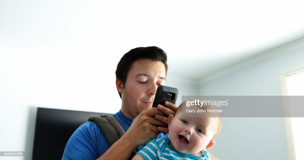 Dad pacing room, texting on phone with baby in baby carrier. : Stock Photo