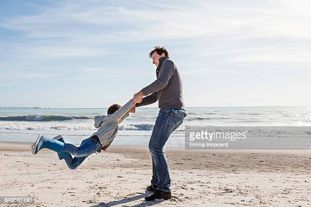 Dad playing and swinging son around on seashore