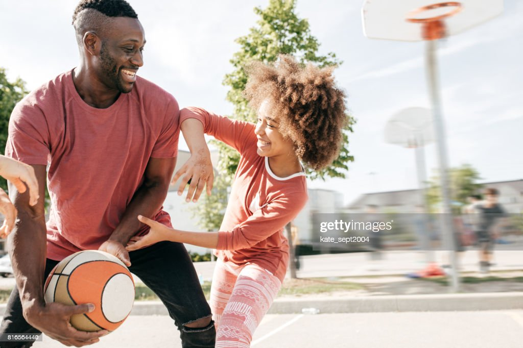 Dad playing basketball with daughter : Stock Photo