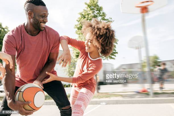 Dad playing basketball with daughter