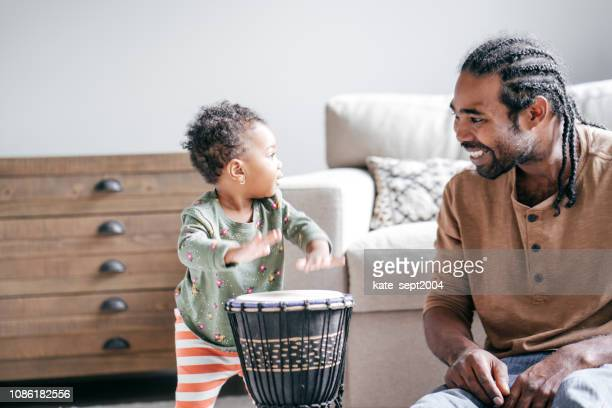 dad playing drums with daughter - family with one child stock pictures, royalty-free photos & images