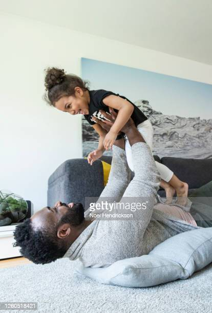 dad playing with his toddler daughter on living room floor - genderblend stock pictures, royalty-free photos & images