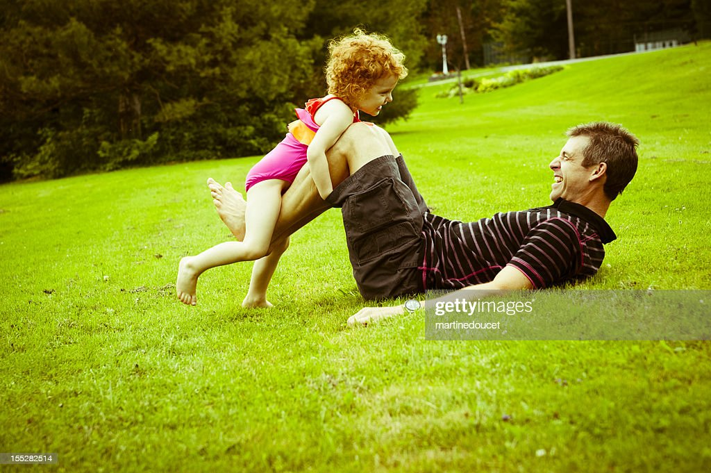 Dad playing with little girl in the field : Stock Photo