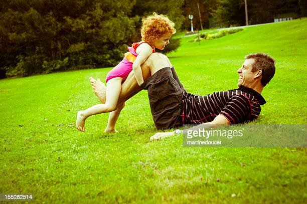 Dad playing with little girl in the field