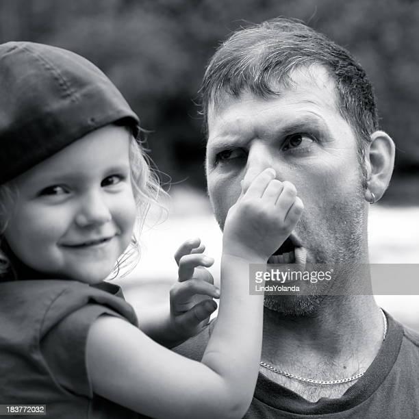 Padre jugando con niña, la cara jocosa
