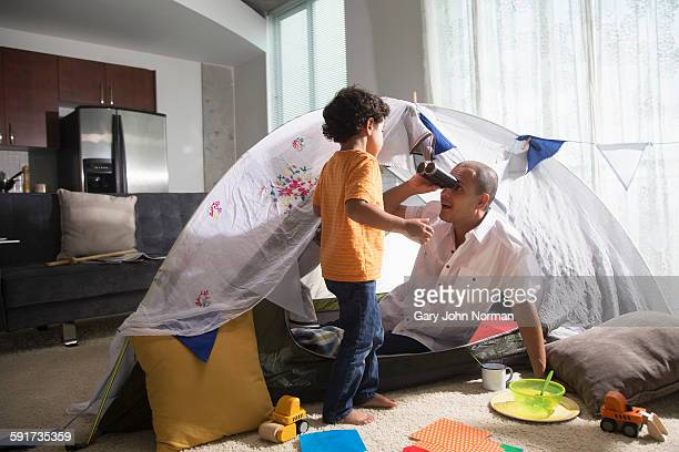 Dad plays at camping indoors with young son