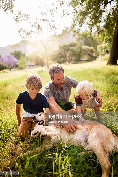 Dad plays with his cute sons and their dog outside