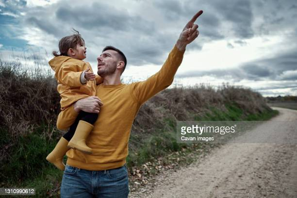 a dad pointing out something to his 2 year old daughter in natur - natur stock pictures, royalty-free photos & images