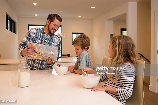 a dad pouring his kids cereal. - leanintogether stock pictures, royalty-free photos & images