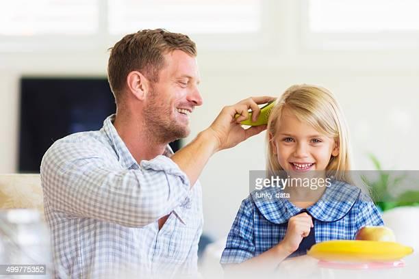 Dad preparing daughter for school
