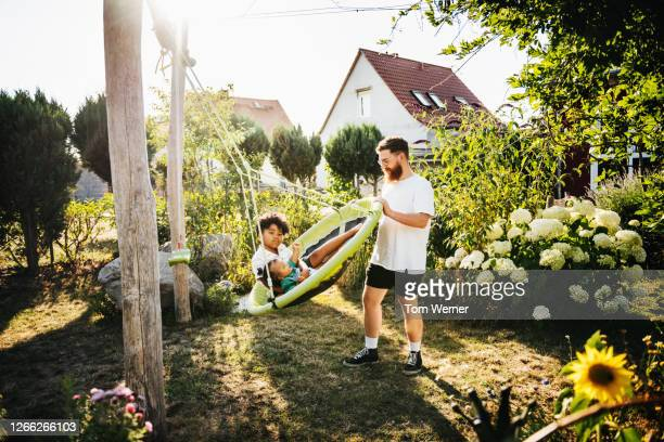 dad pushing kids on swing in back garden together - genderblend stock pictures, royalty-free photos & images