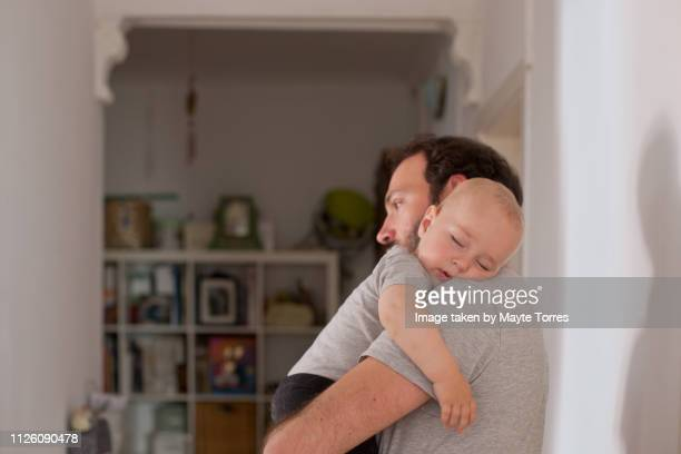 dad putting to sleep baby boy in his arms - carrying imagens e fotografias de stock