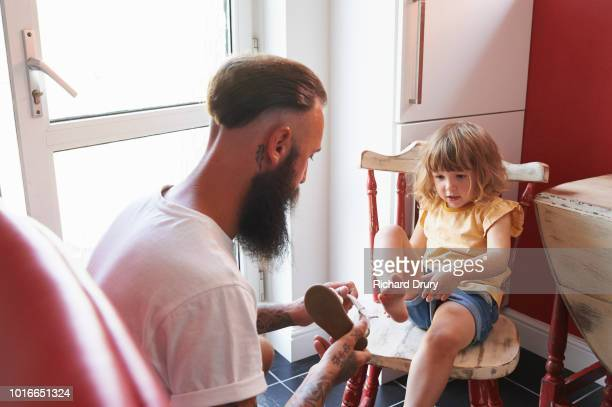 dad putting toddler daughter's sandals on - stay at home father stock pictures, royalty-free photos & images