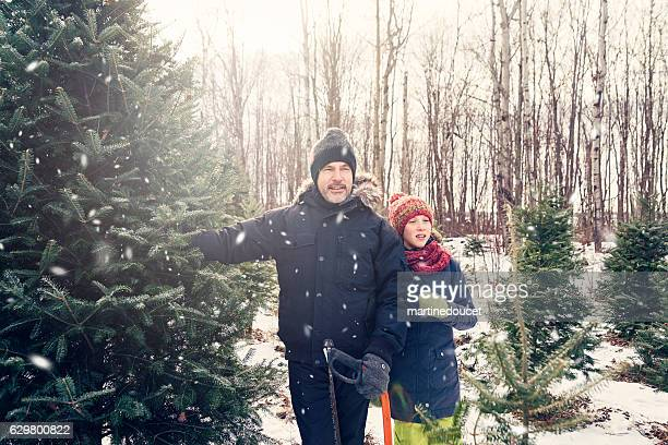 """dad ready to cut the perfect christmas tree outdoors winter. - """"martine doucet"""" or martinedoucet fotografías e imágenes de stock"""