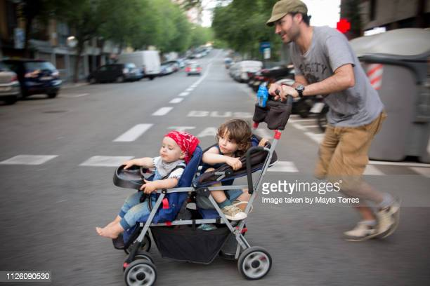 dad running with a double stroller - autism awareness stock pictures, royalty-free photos & images