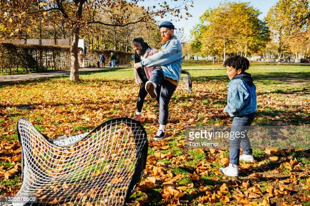 dad scoring goal while playing soccer with family - shooting at goal stock pictures, royalty-free photos & images
