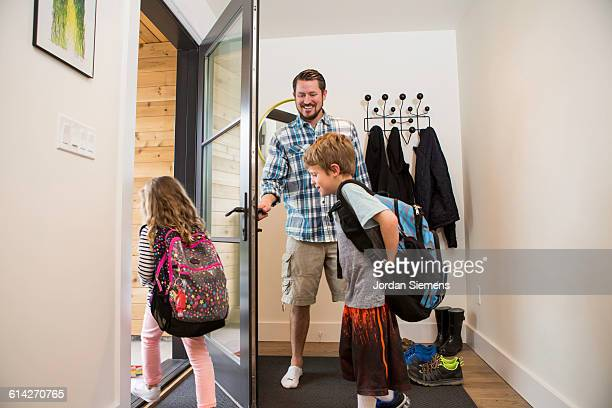 A dad seeing his kids off to school.