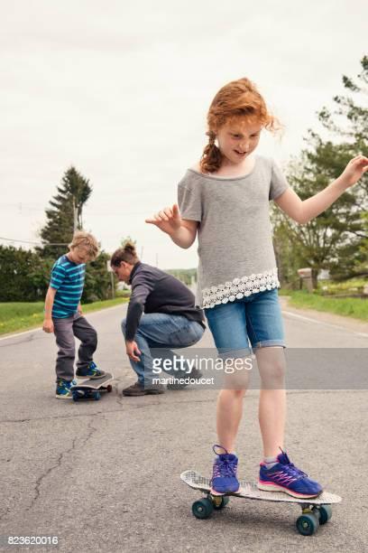 "papá enseña a los niños a monopatín en la calle rural - ""martine doucet"" or martinedoucet fotografías e imágenes de stock"