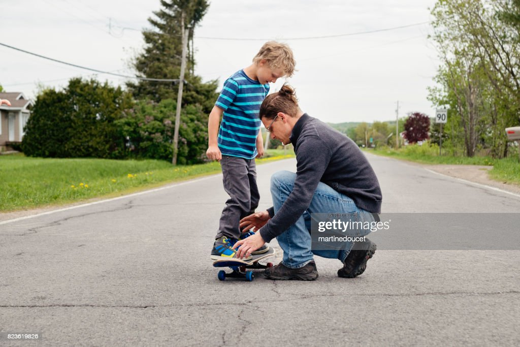 Dad showing son how to skateboard in rural street : Stock Photo