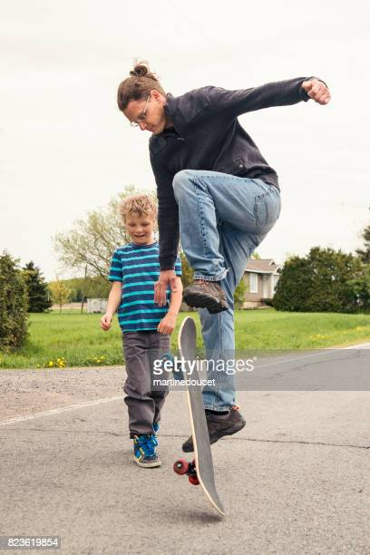 Dad showing son how to skateboard in rural street.