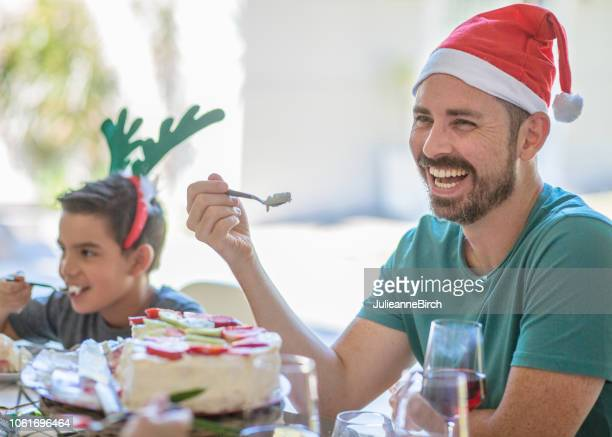 dad smiling and laughing at table over christmas lunch - lunch stock pictures, royalty-free photos & images