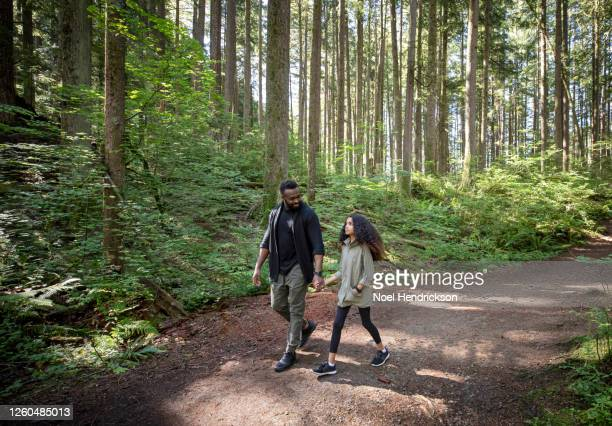 dad smiling to his daughter on the forest trail - canada stock pictures, royalty-free photos & images