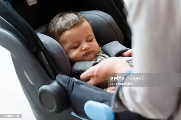 お父さんは車の座席に赤ちゃんをストラップ - バックル ストックフォトと画像