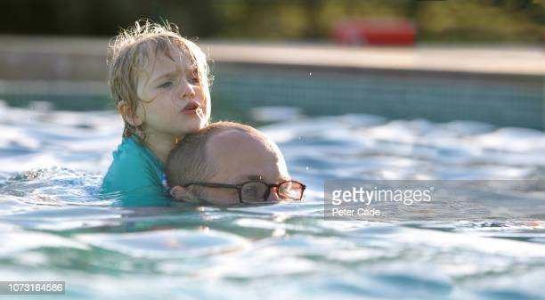 dad swimming with daughter on his back in swimming pool - prop stock pictures, royalty-free photos & images