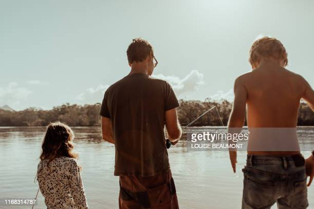 dad takes over the rod for a while - simple living stock pictures, royalty-free photos & images