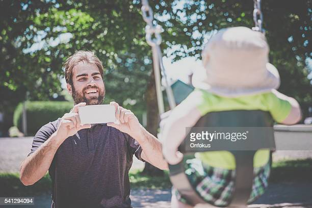 Dad Taking Pictures of Baby in Playground Swing Outdoors
