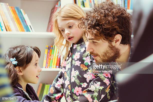 dad talking with girl inside bookshop
