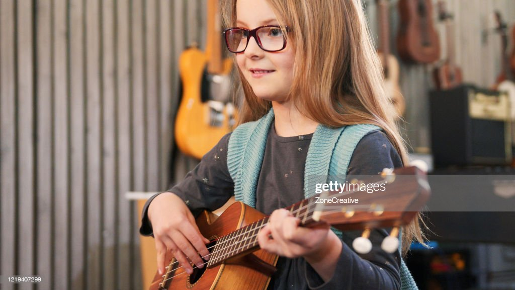 Dad teaching guitar and ukulele to his daughter.Little girl learning guitar at home.Close up.Ukulele class at home. Child learning guitar from her father : Stock Photo