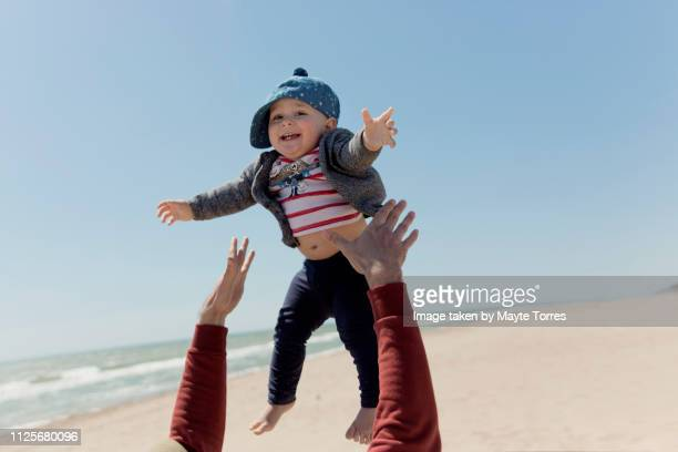 dad throwing baby boy on the air at the beach - catching stock pictures, royalty-free photos & images