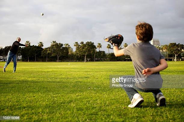 A dad throws a baseball to his kid to catch at the park.