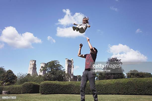dad throws daughter up - vangen stockfoto's en -beelden