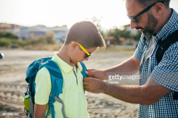 Dad tries to correct his son backpack