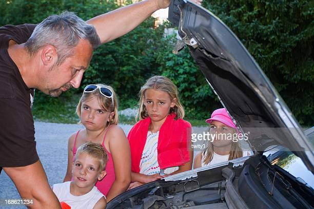 Dad trying to fix broken car while his kids wait sadly
