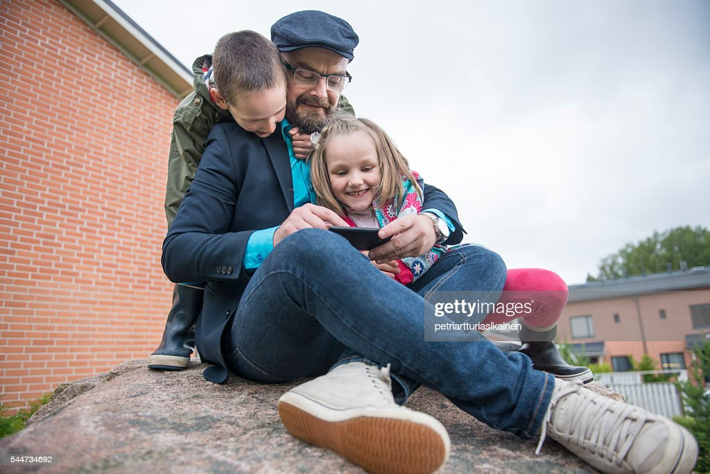 Dad using smartphone with kids. : Stock Photo