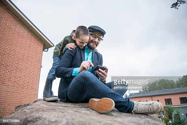 Dad using smartphone with son.