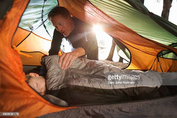 Dad waking sleeping son in tent